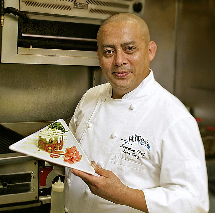 Chef Juan Cruz holding plate of food